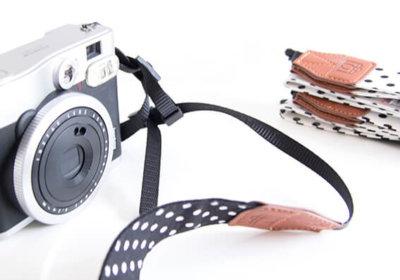 Camerariem bij Polaroid camera in het zwart wit met stippen.