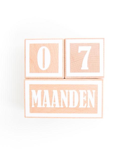 Houten mijlpaal blokken met witte letters en cijfers.
