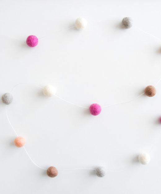 Slinger van vilt bolletjes in lieve pastelkleuren van roze, wit, grijs en beige.