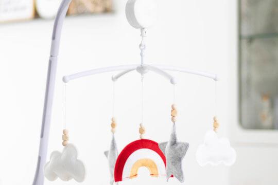 Muziekmobiel aan de box voor baby van vilt met regenboog, wolkjes en sterren.